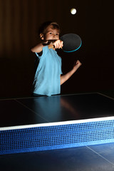 little boy wearing blue shirt playing ping pong;