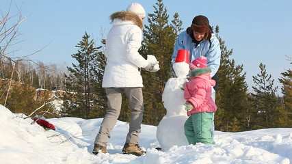 Family of three spending time outdoors making a snowman