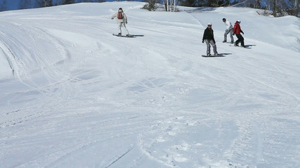 Four snowboarders taking a slow winding ride down the slope