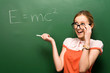 Student standing by chalkboard with e=mc2