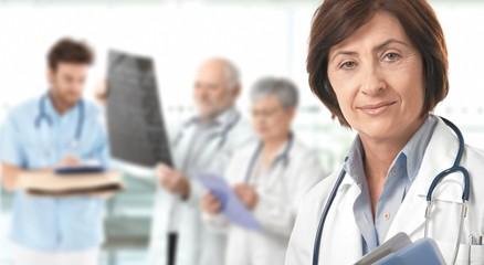 Senior female doctor medical team in background