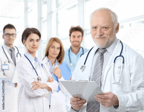 Portrait of aged doctor with medical residents