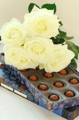 A box of chocolates and white roses