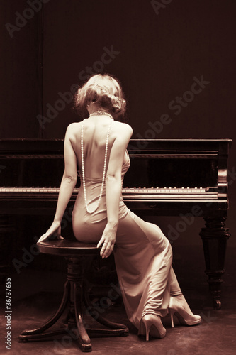 Leinwanddruck Bild beautiful young attractive woman in cocktail dress and piano