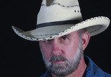 A Man with a Gray Beard in a White Straw Cowboy Hat