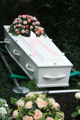 White coffin with pink sympathy flowers