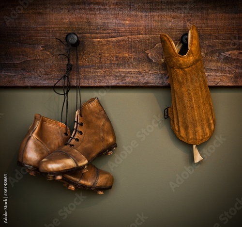 Vintage football boots and shin guard hanging on a locker room