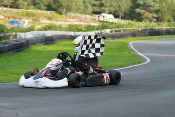 Go kart race winner with chequered flag