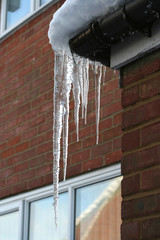 Vertical shot of icicles on a roof