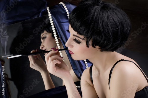 Beautiful girl with cigarette before a mirror