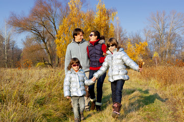 Happy family walking in autumn park. Parents with kids outdoodrs