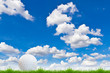 golf ball on green grass against blue sky