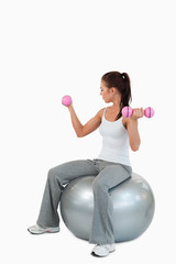 Portrait of a young woman working out with dumbbells and a ball