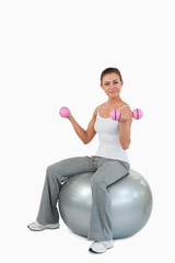 Portrait of a fit woman working out with dumbbells and a ball