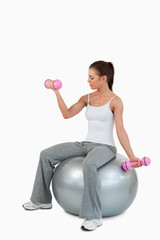 Portrait of a cute woman working out with dumbbells and a ball