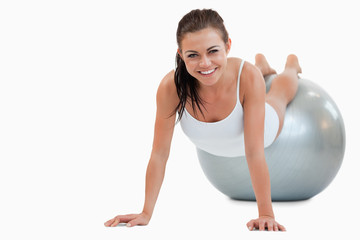 Smiling woman working out with a ball