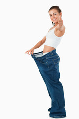 Portrait of a fit woman wearing too large pants with the thumb u