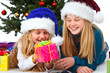 two girl with santa hat and gift smiling