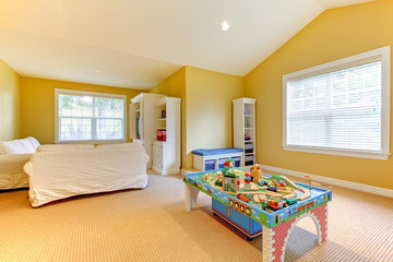 Yellow kids play room with white sofs and beige carpet