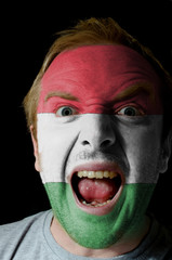 Face of crazy angry man painted in colors of hungary flag