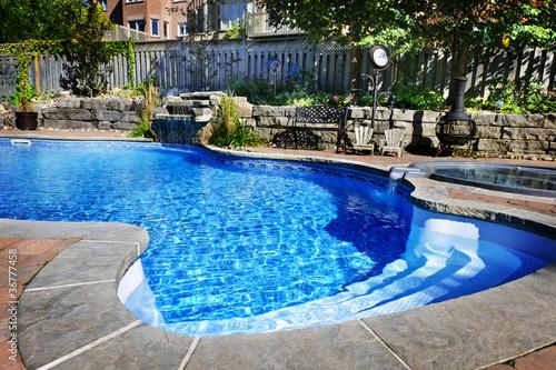 Leinwanddruck Bild Swimming pool with waterfall