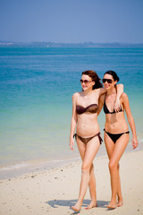 Two young and attractive women walking on the beach