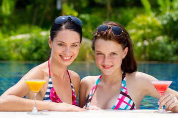 Two young and attractive women having drinks by the pool