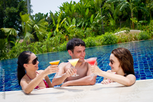 Three friends having drinks by the pool