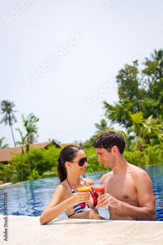 An young and attractive couple having drinks by the pool