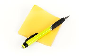 Post-it o pósit y bolígrafo amarillo en fondo blanco.