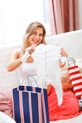 Smiling pregnant sitting on couch with shopping bags
