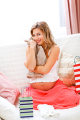 Happy pregnant woman sitting on sofa with shopping bags