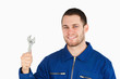 Smiling young mechanic holding his wrench