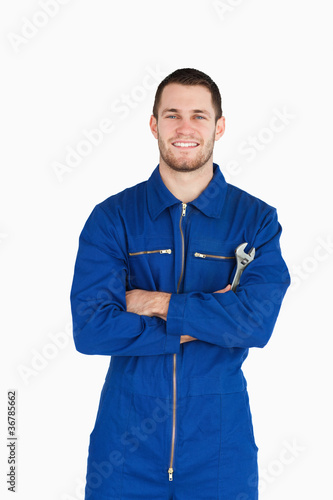 Smiling young mechanic in boiler suit with wrench and arms folde