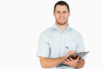 Smiling young post employee taking notes on clipboard