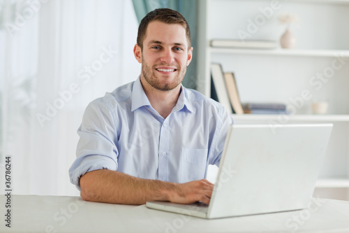 Businessman with rolled up sleeves on his laptop in his homeoffi