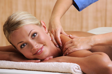 Smiling woman taking massage in beauty salon