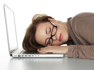 Young business woman sleeping on her laptop at work