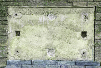 Light-grey concrete wall between a wall of brick stones