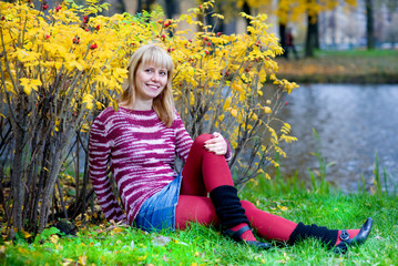 Smiling woman sitting on the river bank