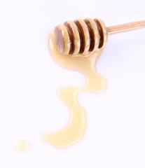 Honey on a honey stick and on a white background