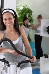 Smiling brown-haired woman on cross trainer