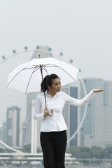 Asian business woman standing under an Umbrella