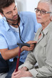 Male doctor giving elderly woman medical check-up