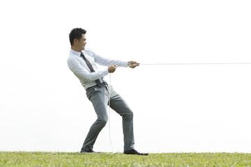Business man playing tug of war