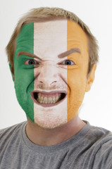 Face of crazy angry man painted in colors of ireland flag