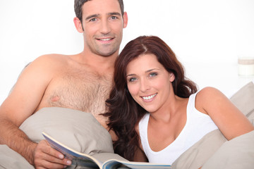 Couple reading a magazine in bed