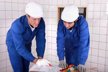 tradesman teaching his apprentice how to read a blueprint