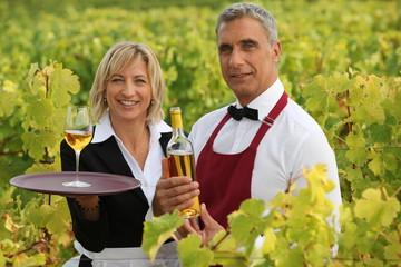 two wine waiters posing in vineyards