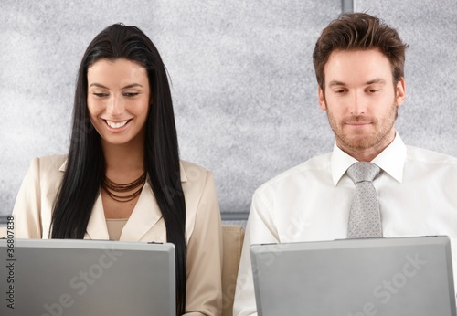 Young colleagues working on laptop smiling